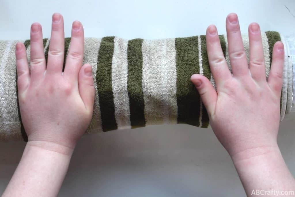 Rolling a towel wrapped around a pool noodle and bubble wrap with the palms of the hands