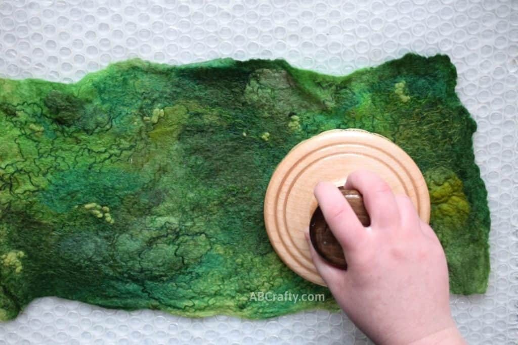 Using a heartfelt silks palm washboard on top of a green wool piece of prefelt to help full and felt the wool