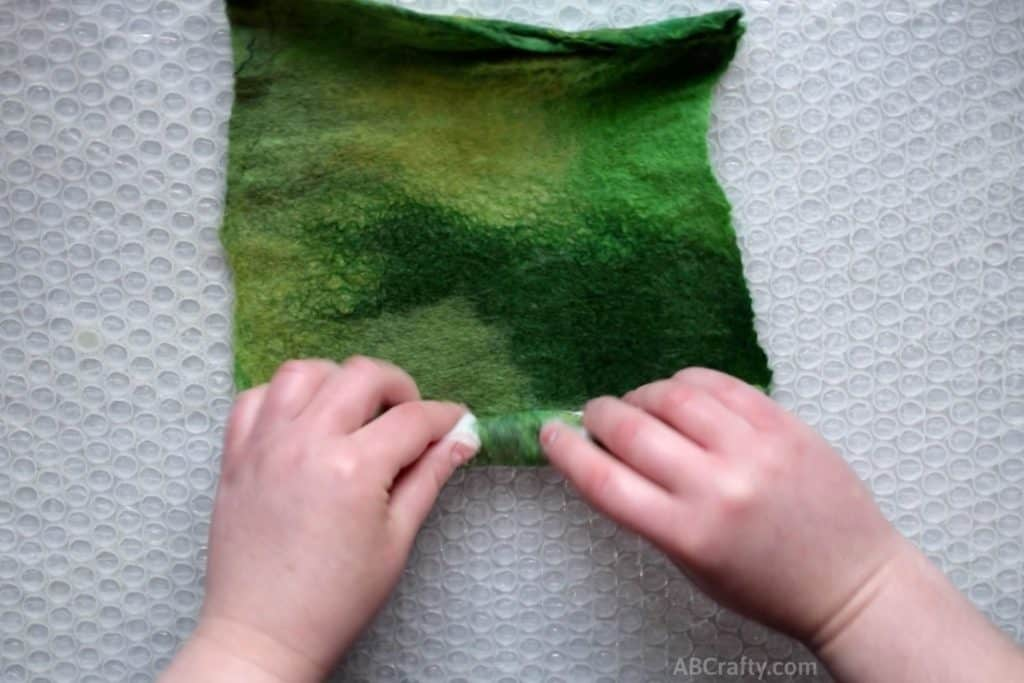Rolling the edge of partially felted green handmade felt