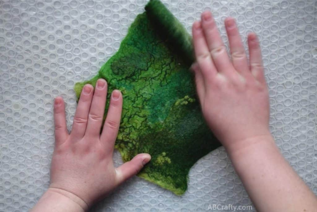 Vigorously unrolling green partially felted green wool fabric from one end