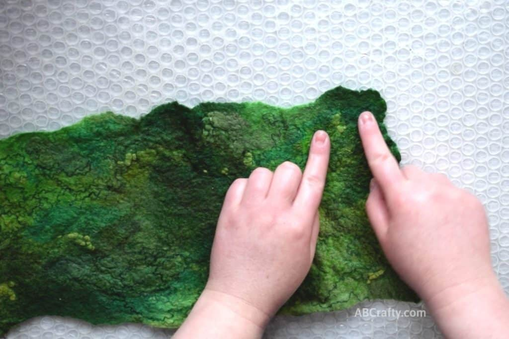Pointing at the corner of partially wet felted green wool fabric with fun texture and designs from other green fibers