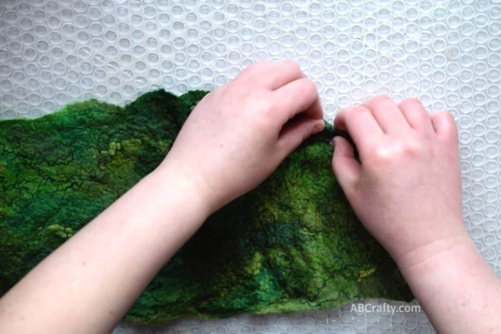 Pinching and rolling the corner of partially wet felted green artful felt fabric
