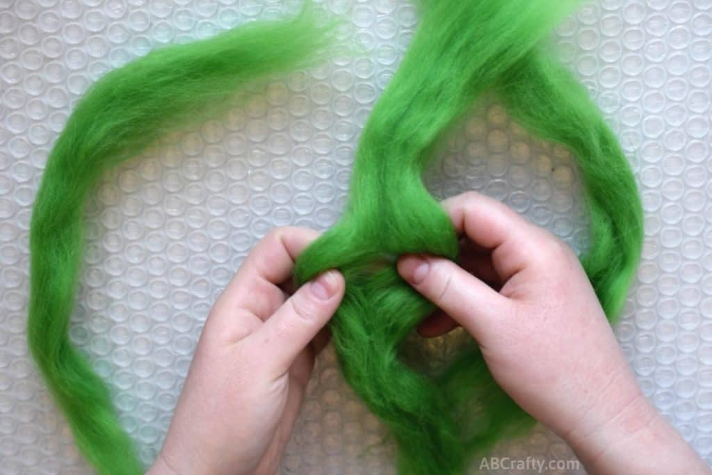 Separate green wool roving in half over bubble wrap