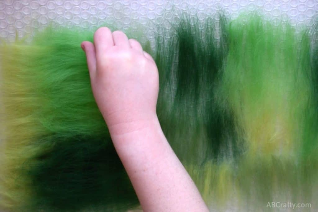 Placing small amounts of green wool roving perpendicular on top of different colors of wool roving that are on top of bubble wrap