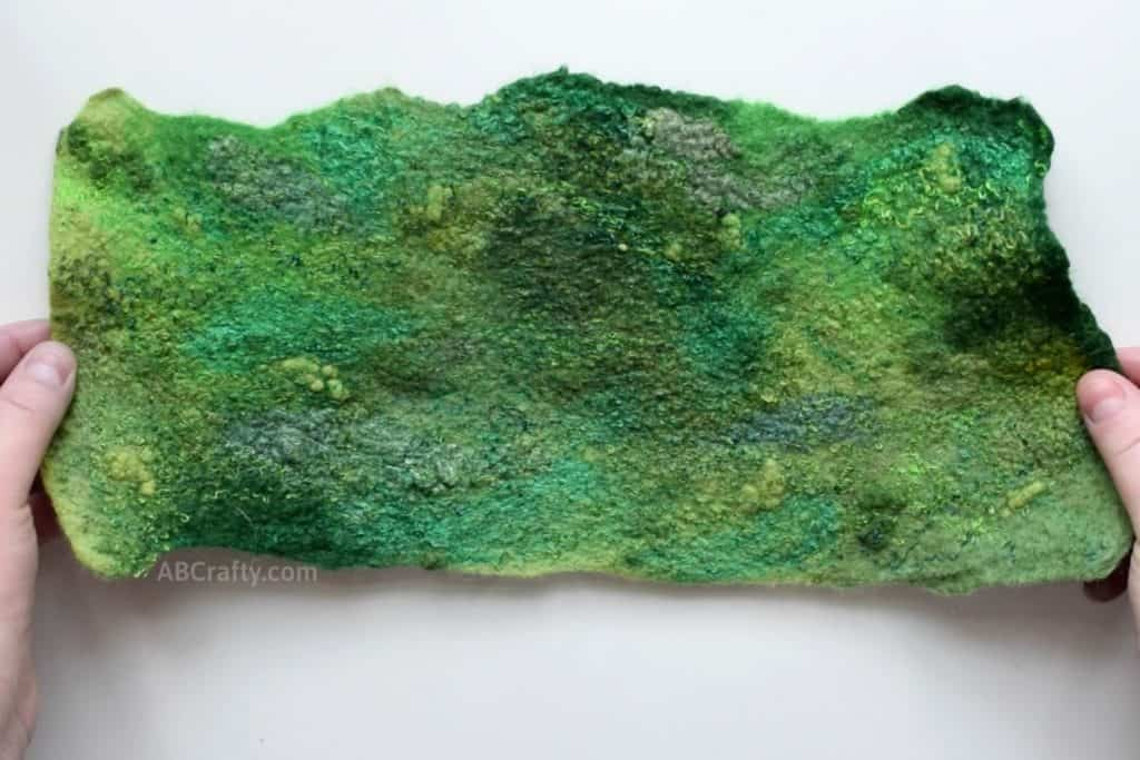 Holding finished piece of handmade wet felted green fabric with swirls of viscose, wool nepps and other embellishment fibers that have been felted into the wool