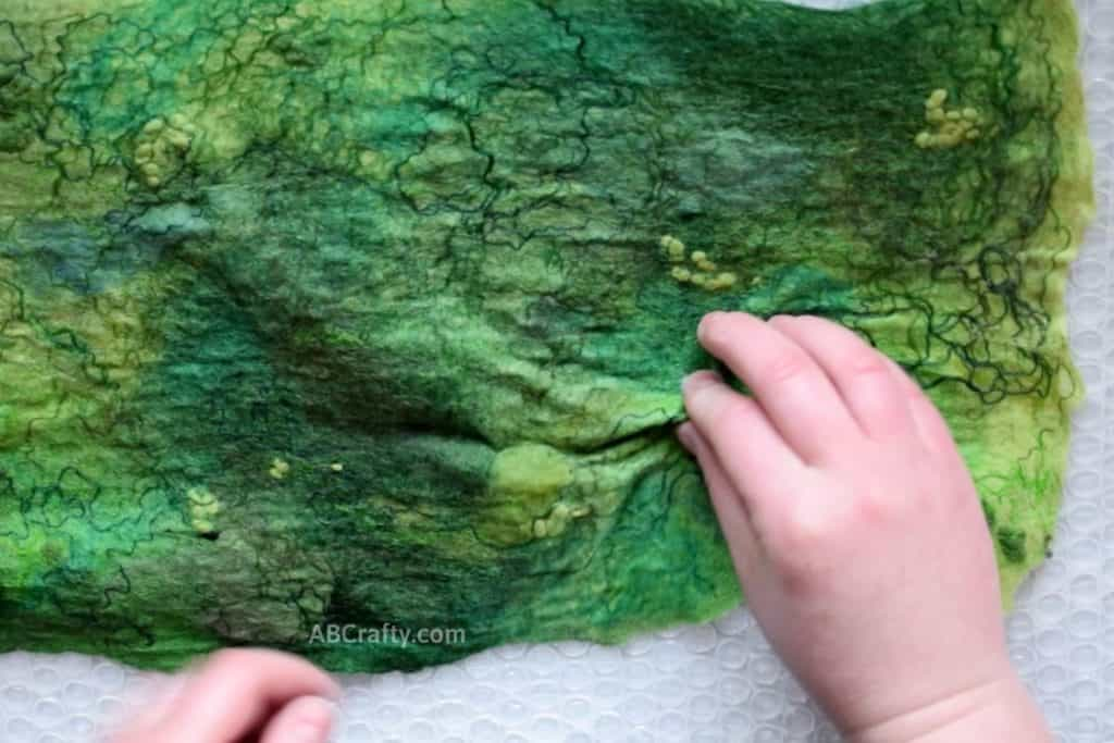 Performing pinch test on prefelt wool that is partially wet felted green wool with various fibers felted into the wool