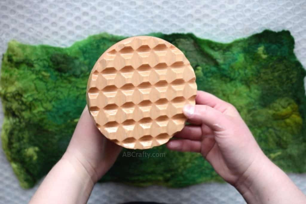 Showing the bottom of a palm washboard from Heartfelt Silks on top of a wet felted piece of green wool fabric