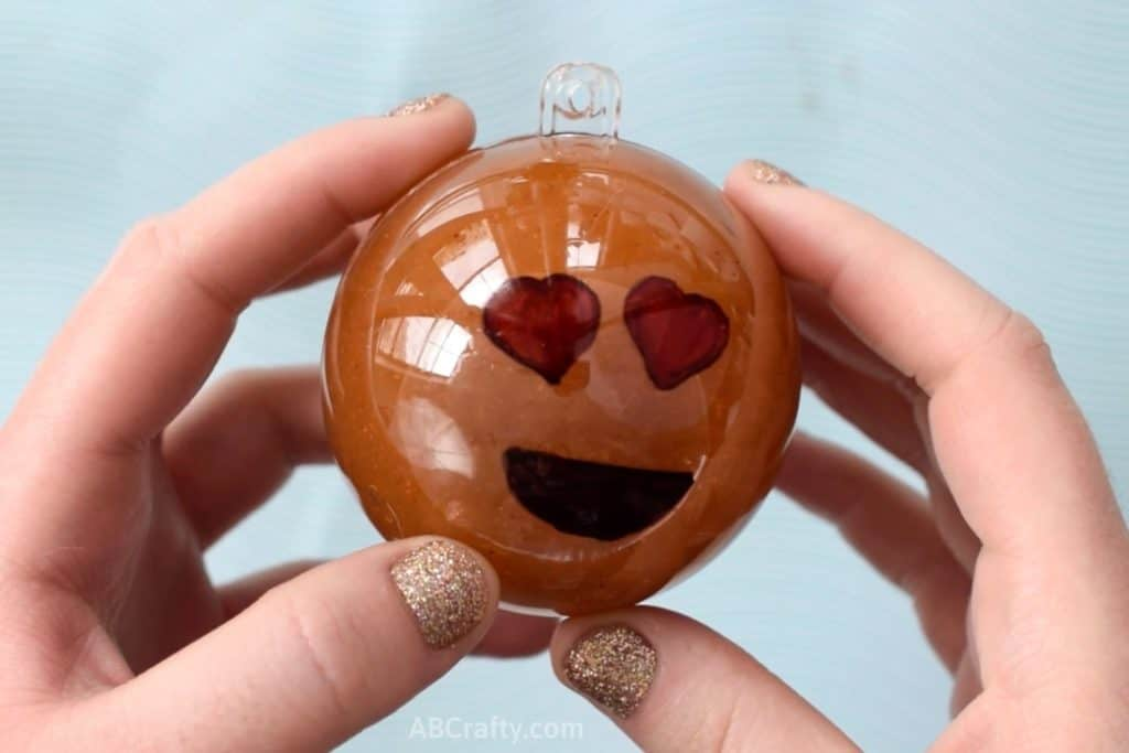 Holding a plastic ornament with a heart eye emoji on it filled with orange