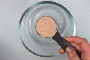 Holding a tablespoon of light brown fiber powder over a clear glass bowl