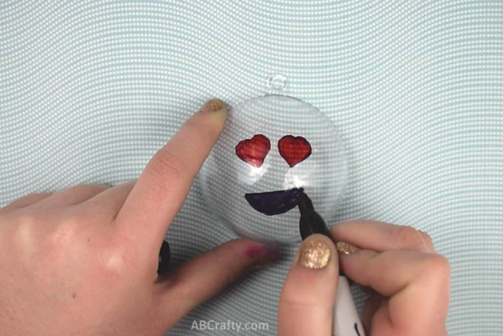 Drawing a black smile onto a heart eyed emoji with a sharpie on top of a plastic ornament