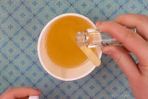 Pouring essential oils into melted soy wax that's in a paper cup with a popsicle stick in it