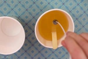 Dipping the metal part of the bottom of a waxed wick into melted wax inside of a paper cup with a popsicle stick in it