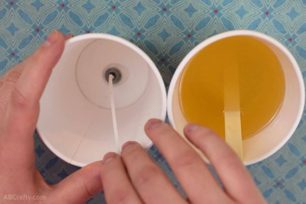 Sticking a waxed wick to the bottom of a paper cup with another paper cup full of melted wax next to it with a popsicle stick in it