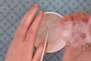 Dropping ice into a paper cup with a candle wick in the middle