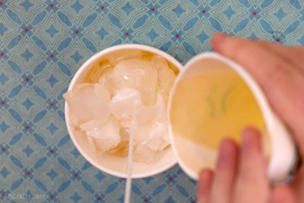 Pouring melted wax out of a paper cup on top of ice cubes with a candle wick sticking out of the middle of a paper cup.