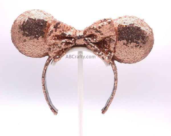 handmade rose gold minnie mouse ears on a white stand