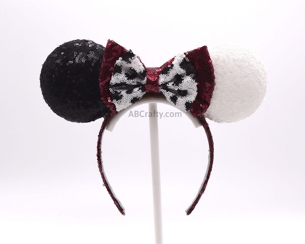 Finished diy cruella deville ears inspired by the disney movie 101 dalmatians and Cruella. One ear has black sequin fabric and the other white sequin fabric with a red minnie mouse bow with a white bow in front of it with black spots. The headband is covered in red sequin fabric.
