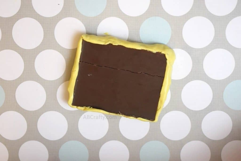 back of half of a hershey's chocolate bar with yellow mold putty around it