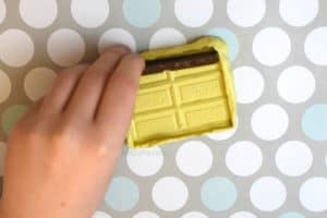 Removing broken chocolate from a yellow diy chocolate bar mold made from a hershey's bar
