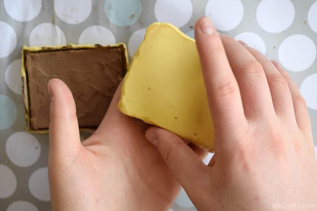 yellow silicone mold flipped over with one hand onto another hand