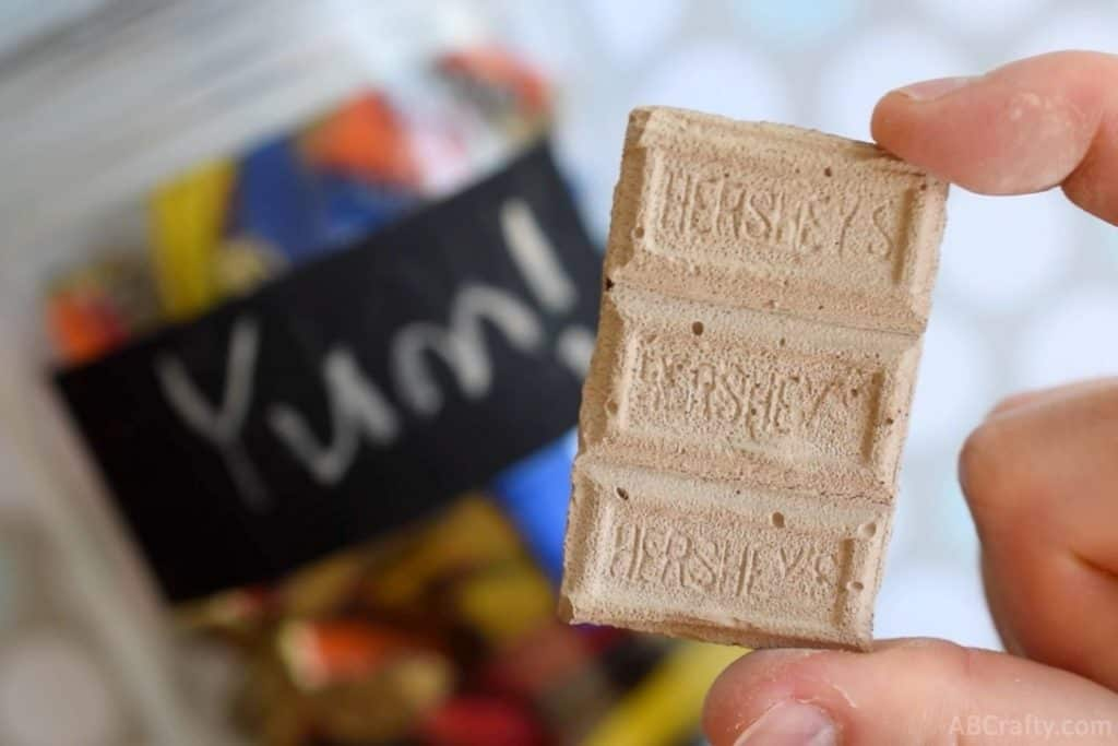 holding a small piece of diy chocolate chalk with a glass jar in the background that has a chalkboard label with 'yum' written on it