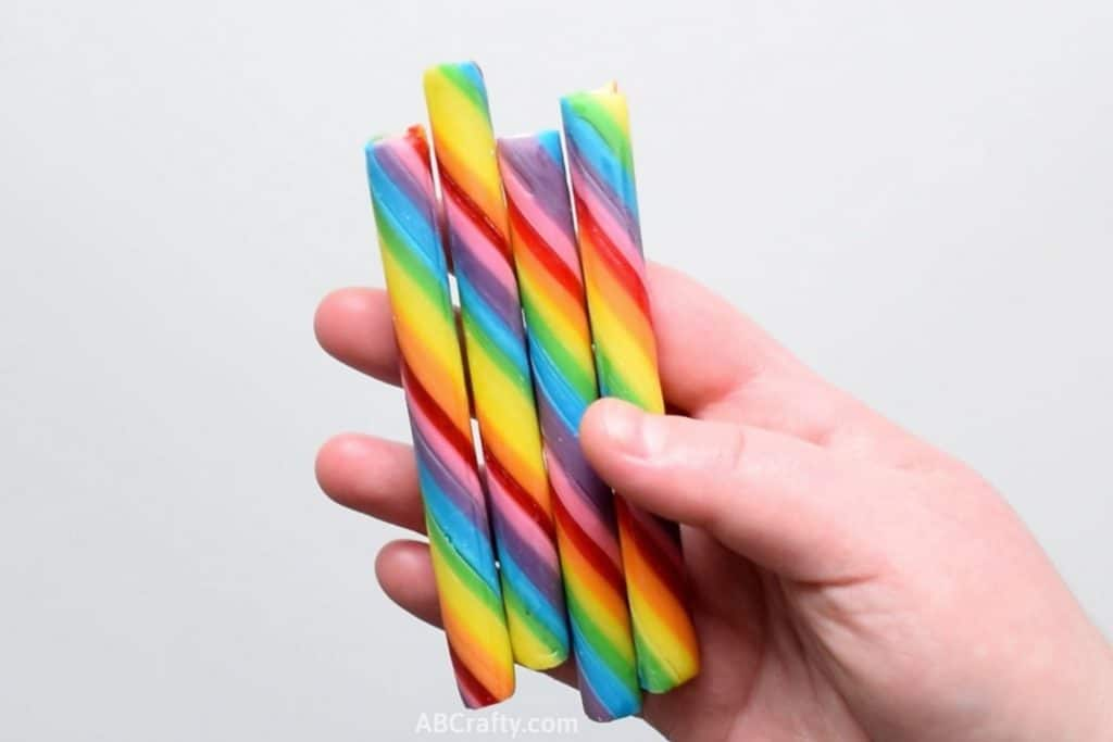 Holding rainbow candy sticks