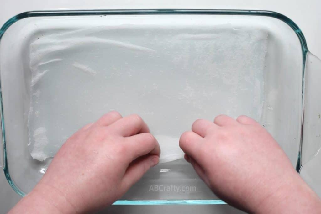 Stretching a damp habotai scrap flat across in a clear pyrex dish