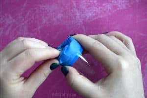 Taping the bottom of a shot glass with blue painters tape
