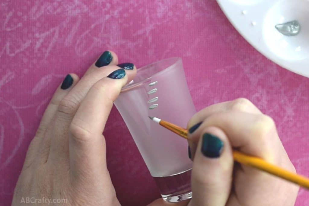 Starting to paint a zipper design onto a shot glass using silver acrylic paint