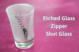 "Zipper design painted silver on an etched glass frosted shot glass with a zipper pull attached. The title reads ""etched glass zipper shot glass"""