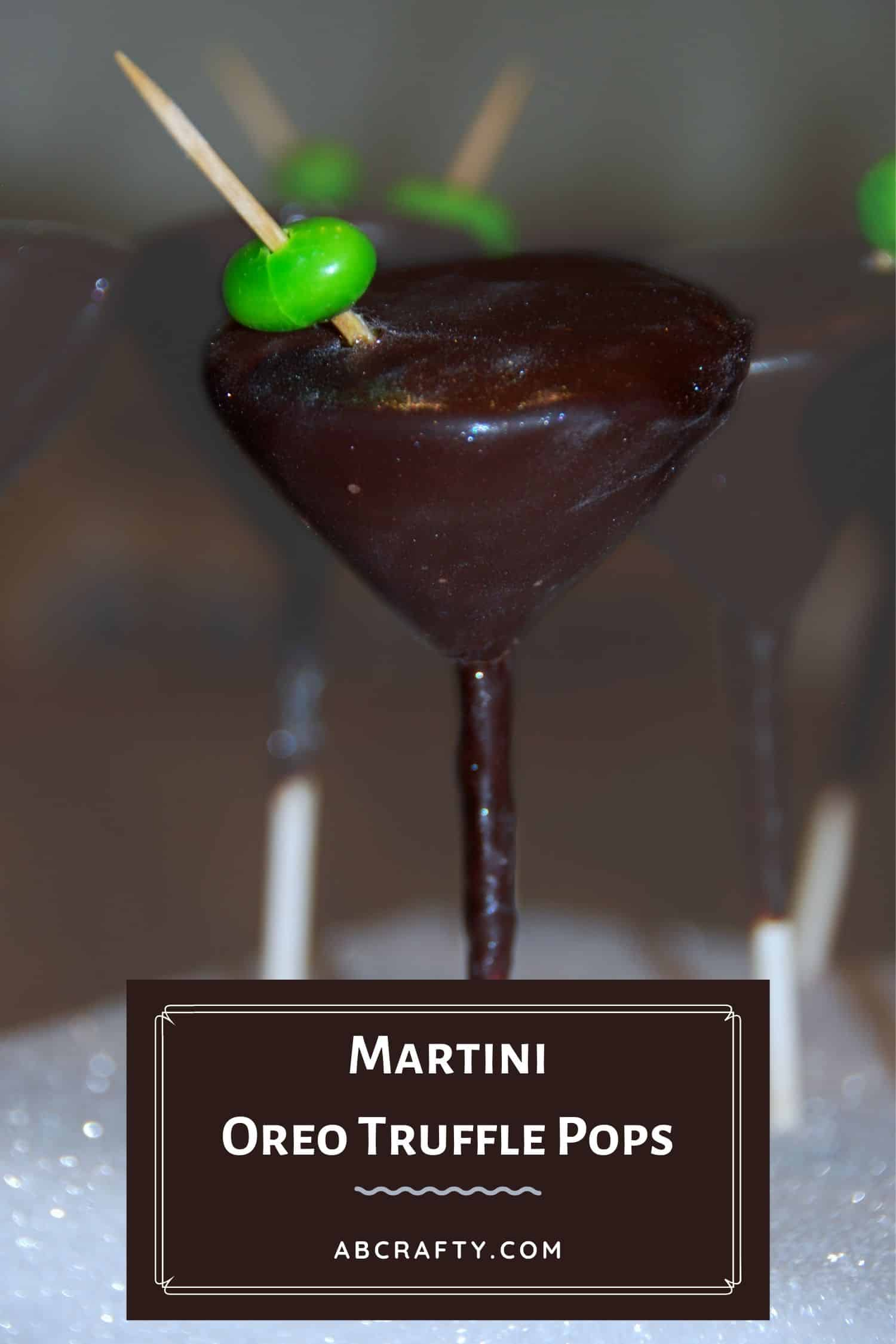 Martini glass cake pop made of oreo balls. It's on a cake pop stick, covered in chocolate with a green jelly bean as the olive on a toothpick. Title reads 'martini oreo truffle pops, abcrafty.com'