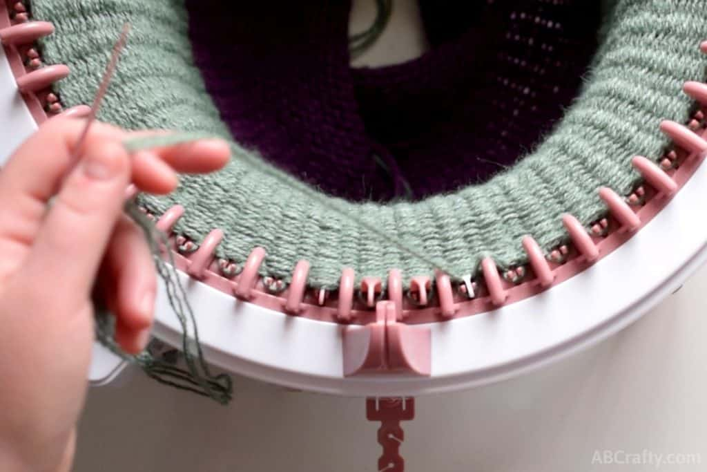 green yarn looped onto a pink plastic needle