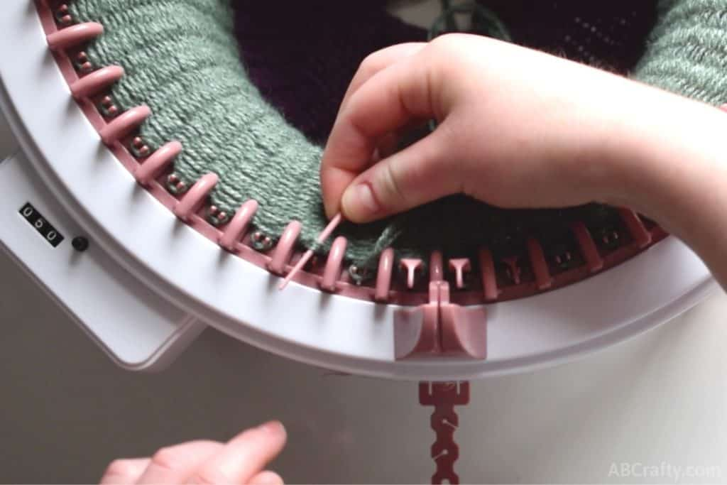 Pink plastic needle going through a loop of green yarn to the left of the yarn holder on the sentro knitting machine
