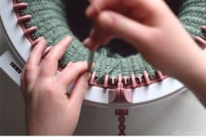 pulling the needle through the loop so the yarn pulls through