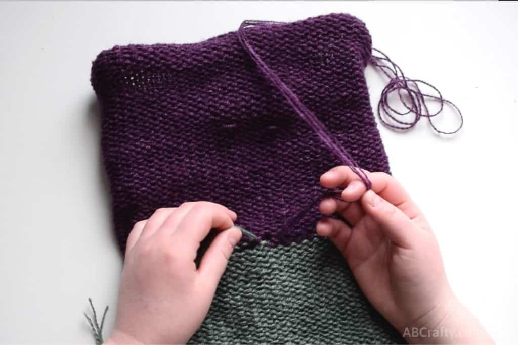 With the purple and green knit tube inside out, tying the ends of each color together in a knot