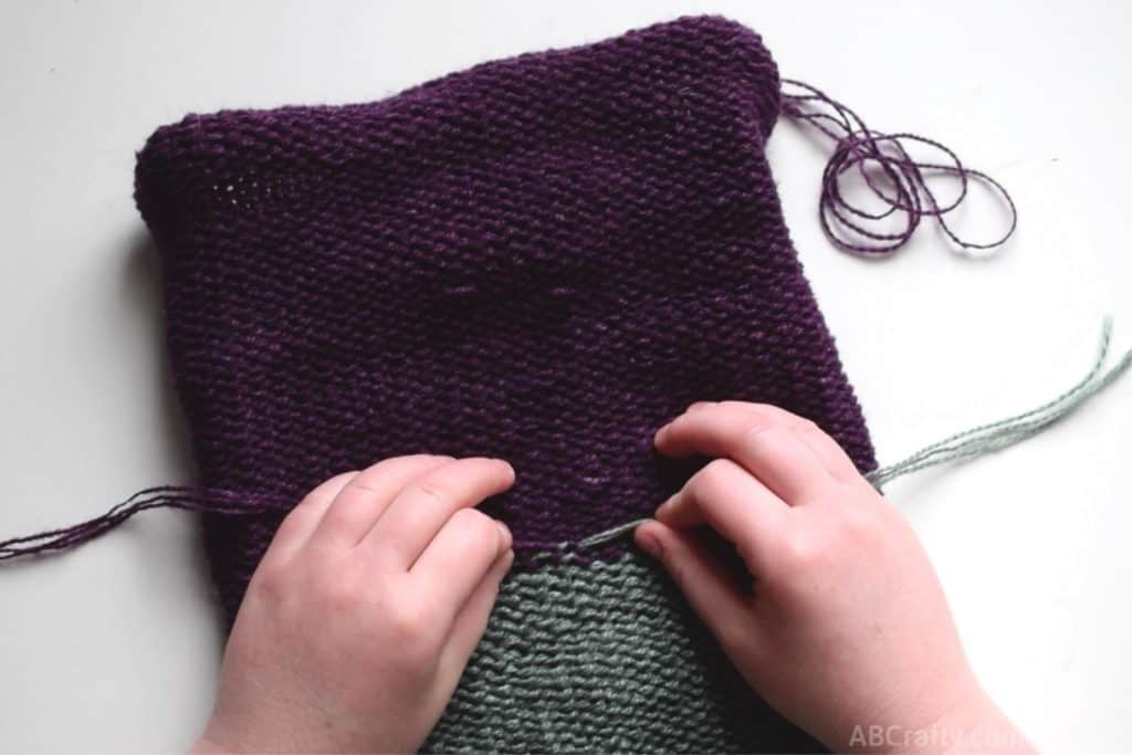 pulling the knot of purple and green yarns tight