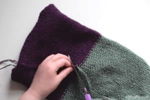 cutting the ends of the purple and green yarn after tying the knot
