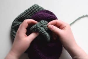 pulling the green side of the knit tube through the middle and part of the way out the purple and pulling the end of the green yarn to make the circle close