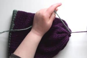 tying the ends of the purple and green yarn together so that the purple end closes up