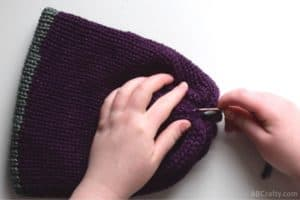 using the plastic needle to sew into the middle of the reversible knit beanie