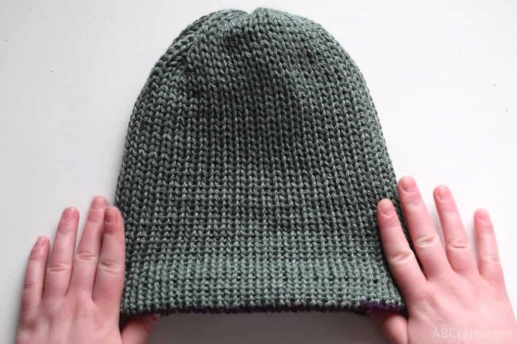 holding the handmade knit hat with the green side facing out