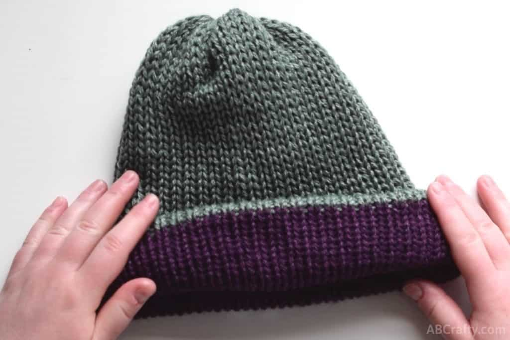 rolling the reversible knit hat part way inside out so the purple from the inside shows, giving the green hat a purple brim