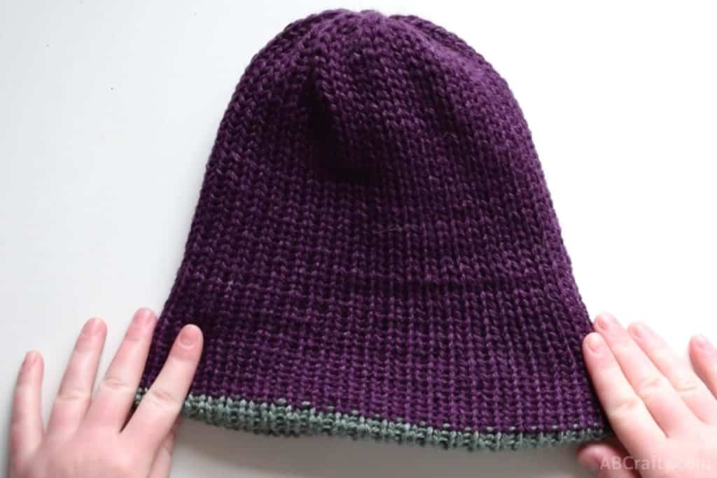 holding the handmade knit beanie with the purple side facing out