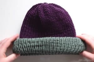 rolling the brim of the knit beanie so the green from the inside is facing out on top of the purple