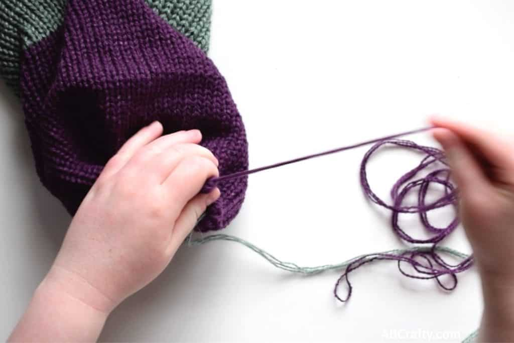 Pulling on purple yarn to close the end of a reversible knit beanie