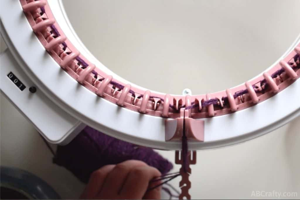 pulling the strands of yarn through the first loop of the tensioner on the sentro knitting machine