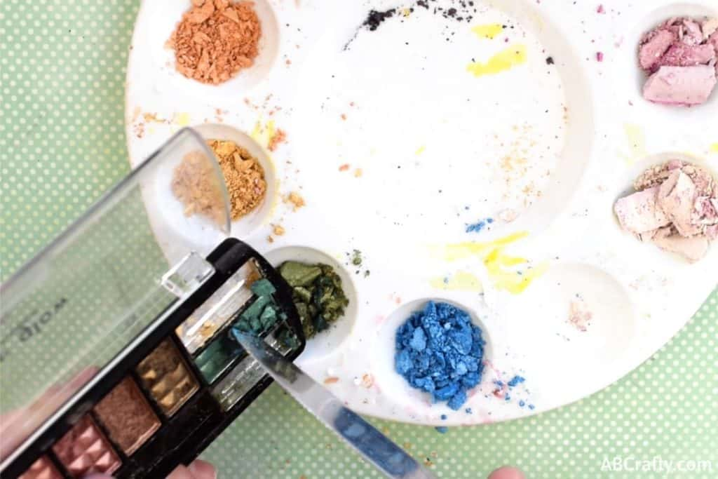 scraping green eyeshadow out of a profusion eyeshadow palette into a mixing palette