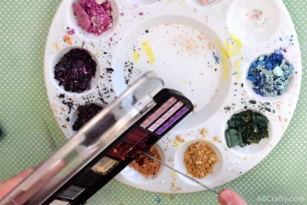 scraping orange eyeshadow into a mixing palette