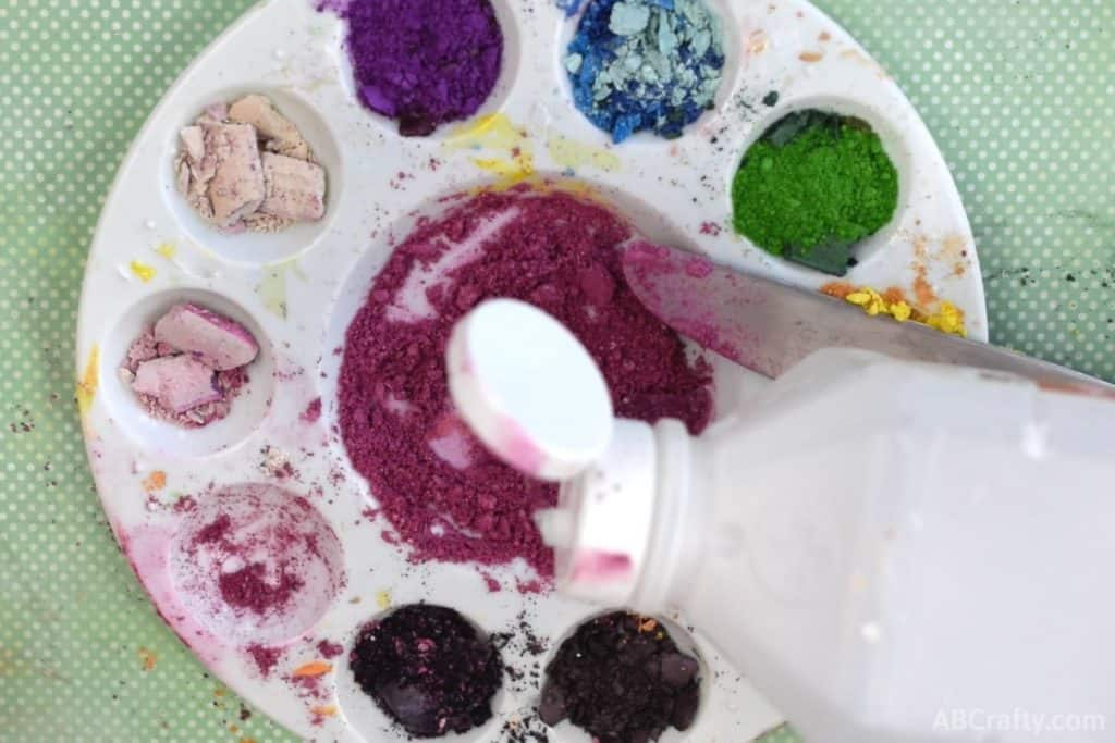 adding rubbing alcohol to pink eyeshadow in a mixing tray
