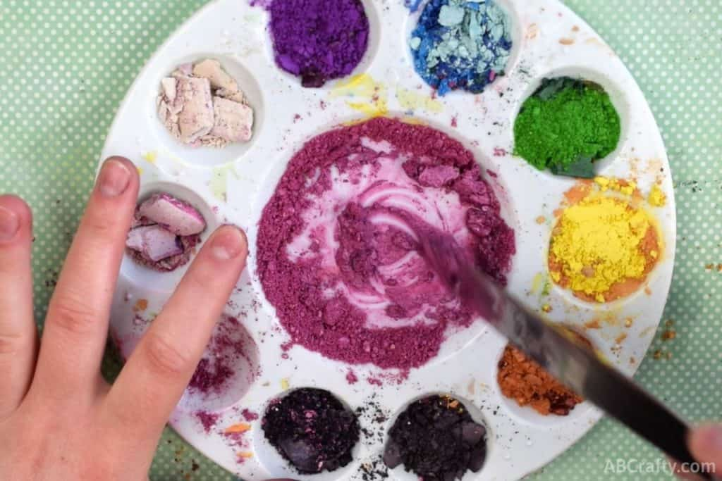 mixing pink eyeshadow and rubbing alcohol to form a paste